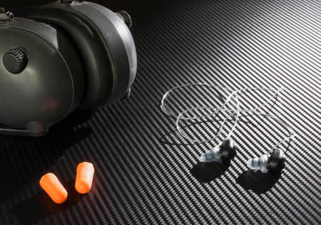 hearing protection: Three different types of devices to protect hearing on a graphite looking background