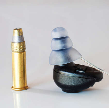 earpiece: Small digital unit to protect your ears next to a .22 cartridge for scale Stock Photo