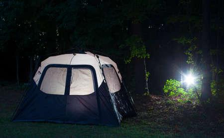 Flashlight headed toward a well lit tent after dark