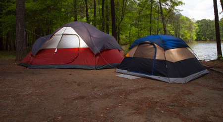 pitched: Two tents that are pitched in a campsite next to a lake