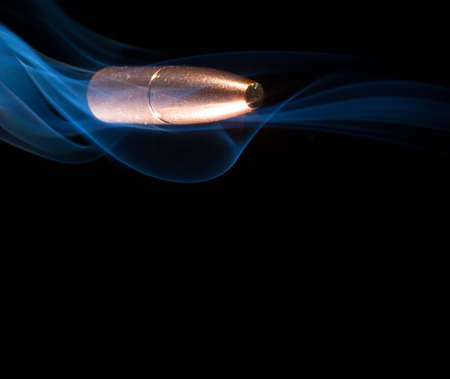 ballistic: Copper plated bullet cruising in a cloud of smoke with a black background