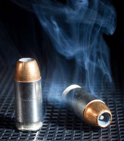 metal grate: Smoke rising from near a pair of hollow point handgun cartridges Stock Photo