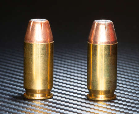 handguns: Copper plated bullets with hollow points on a cartridge for handguns