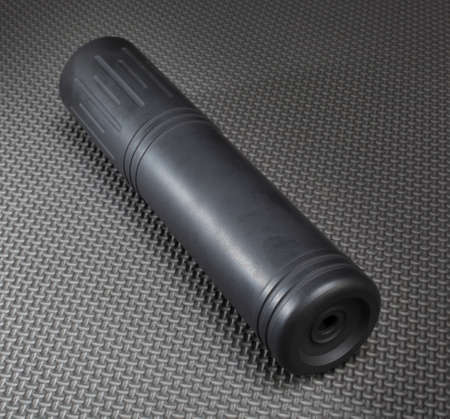 Suppressor that is black and grey on a textured background