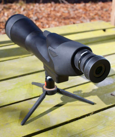 high powered: High powered scope that is set up on a wooden bench
