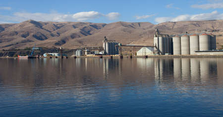 lewiston: Multiple grain elevators and barge on a river near Lewiston Idaho Stock Photo