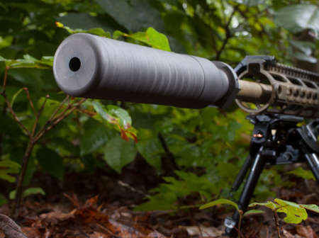Suppressor that is mounted on a rifle that is in the bushes 版權商用圖片 - 46652441