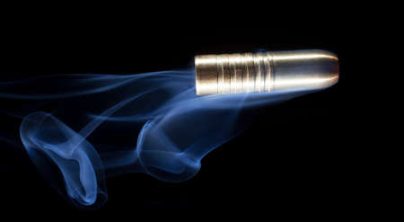 big behind: Big bullet that has smoke behind on a black background Stock Photo