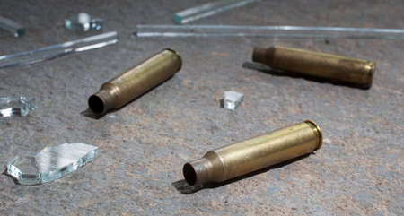casings: Three rifle casings with glass that are on concrete