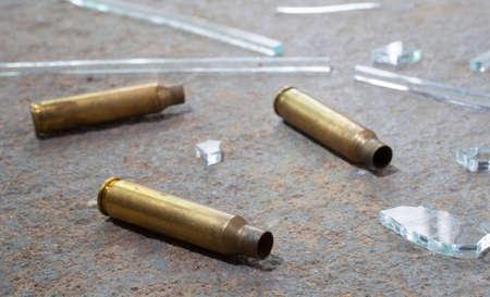 cristal roto: Vidrios rotos y latón rifle que están en el concreto Foto de archivo