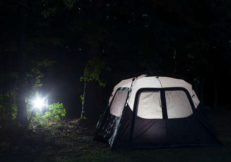 Bright light coming from the forest toward a lighted tent
