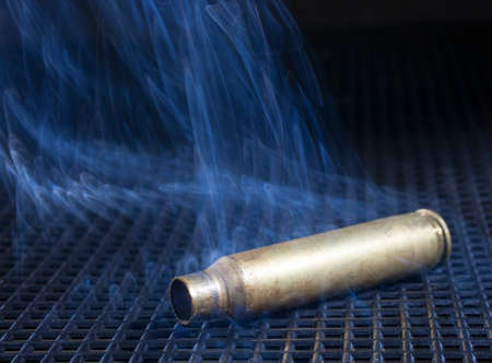 grate: Empty rifle brass on a black grate surrounded by smoke