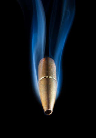 projectile: Bronze colored bullet and smoke coming toward the viewer Stock Photo