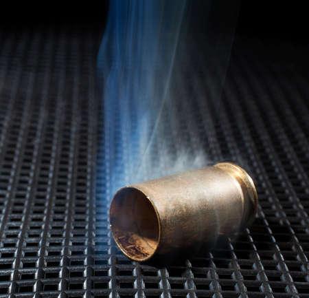 has been: Handgun brass that has been shot with smoke all around Stock Photo