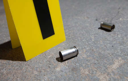 bullet proof: Evidence marker next to two empty handgun cartridges on concrete