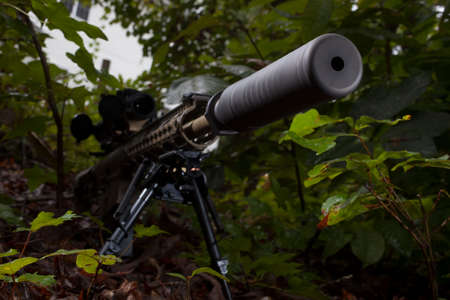 suppressor: Modern sporting rifle in the trees with a suppressor attached Stock Photo