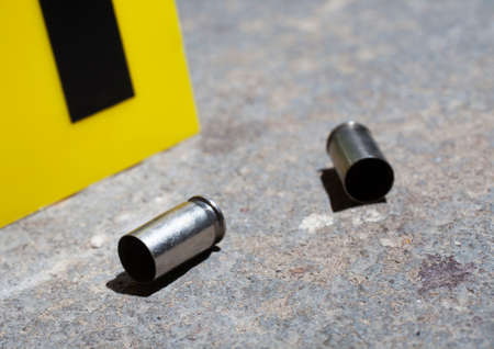 bullet proof: Pair of handgun casings that are on concrete with an evidence marker