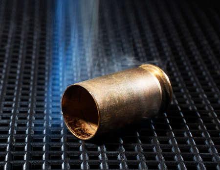 grate: Handgun brass on a dark grate with smoke around Stock Photo