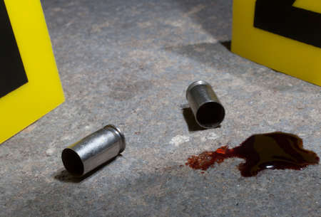 Empty handgun brass with blood and evidence markers on concrete in the night 版權商用圖片