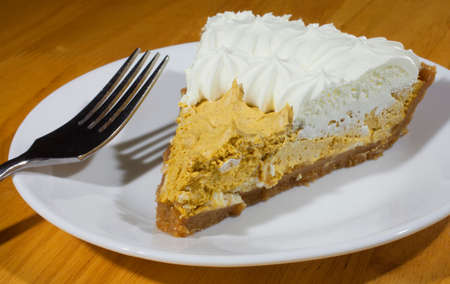 pumpkin pie: Thick piece of whipped pumpkin pie with cream on top Stock Photo