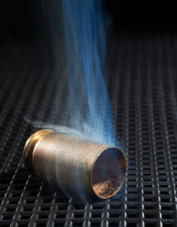 grate: Brass from a handgun on a black grate with smoke