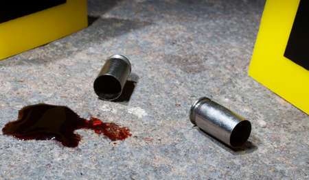 bullet proof: Blood and empty handgun ammo with evidence markers on concrete Stock Photo