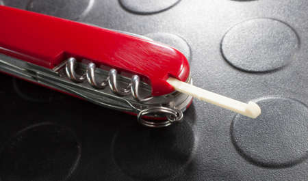 toothpick: Toothpick that slides out of a red multiple purpose knife Stock Photo