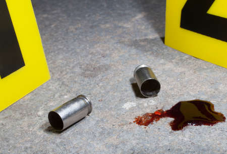 bullet proof: Two empty handgun shells with blood and evidence markers on concrete