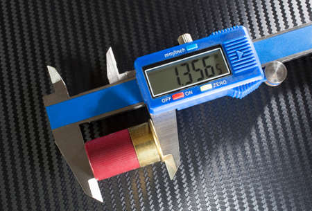 readout: Digital caliper that is measuring the length of a twelve gauge shotshell