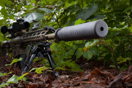the silencer: Camoflauge modern sporting rifle with a silencer on the barrel