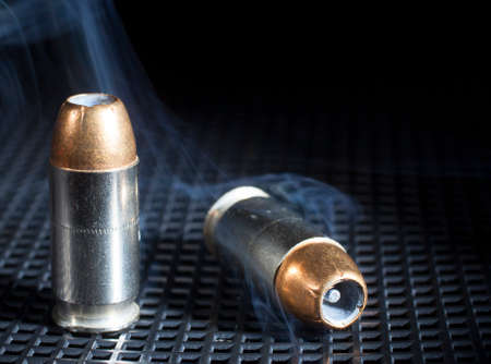 Two hollow point cartridges for a handgun with smoke