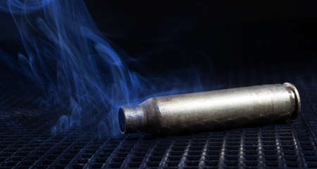 grate: Empty rifle cartridge on a grate with lots of smoke