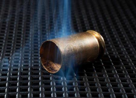 grate: Handgun brass on a black grate with smoke around