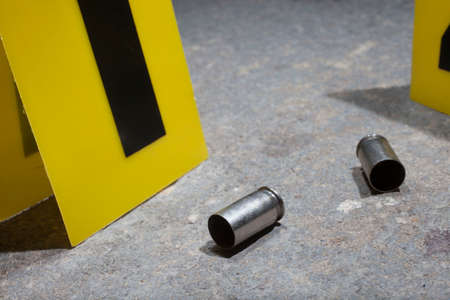 bullet proof: Empty handgun brass on concrete with yellow evidence markers