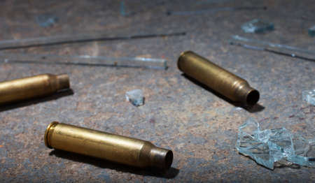 Three rifle cartridges on concrete with broken glass