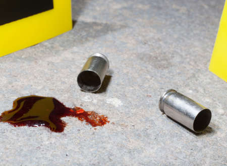 casings: Handgun casings and blood on concrete with crime scene markers Stock Photo