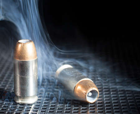 metal grate: Two small cartridges for a handgun with smoke around Stock Photo