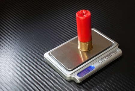 measured: Red twelve gauge ammunition being measured on a digital scale