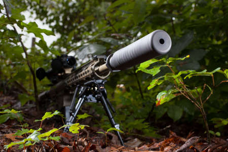 the silencer: High powered rifle with a silencer in the forest