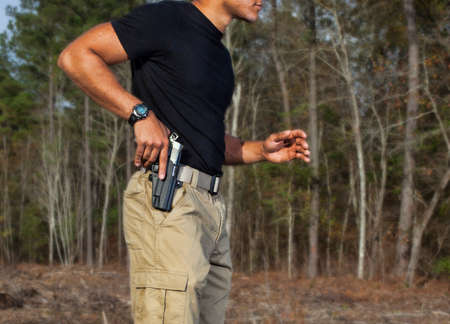 holster: Handgun being drawn from a holster with a forest background