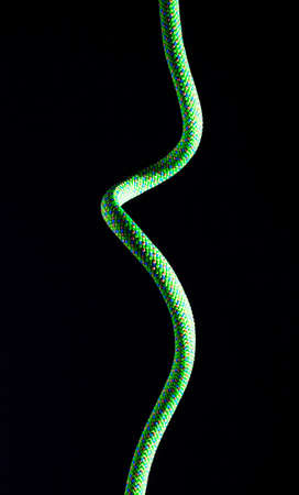 rappelling: Bright green rope that is vertical on a black background