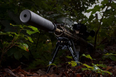 Semi automatic rifle with a suppressor in some dark trees