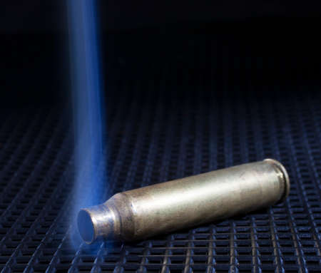 the casing: Brass casing from a rifle that has been shot and is pouring out smoke Stock Photo