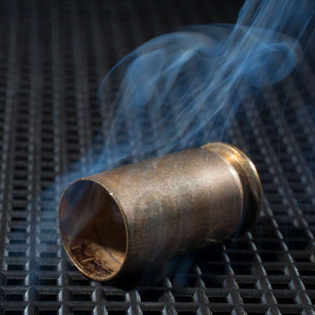 the casing: Handgun casing that has been shot and is smoking on a grate