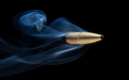 Bullet with a copper finish that has smoke trailing behind
