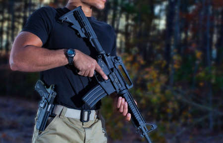 Man with a semi automatic rifle and handgun in the woods Standard-Bild