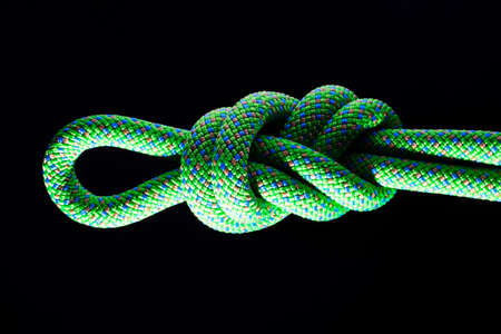 rappelling: Figure eight in a green climbing rope with a black background Stock Photo