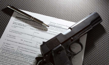 Handgun and pen and paperwork required for the background check for a gun purchase 版權商用圖片