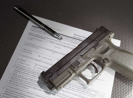 paper texture: Semi automatic handgun and paperwork for a background check for the sale Stock Photo