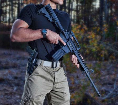 Der Mann mit einer Pistole und einem AR-15 in den Wald Standard-Bild - 50773515
